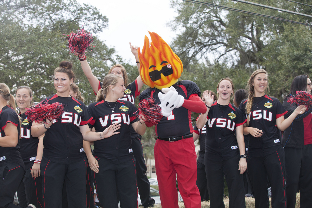 Members of the softball team ride on a parade float with VSU mascot